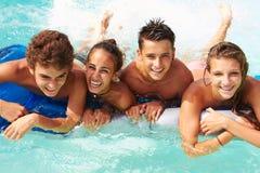 Grupp av tonårs- vänner som har gyckel i simbassäng Royaltyfri Fotografi