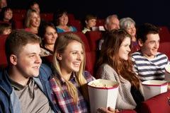 Grupp av tonårs- vänner som håller ögonen på filmen i bio Royaltyfri Fotografi
