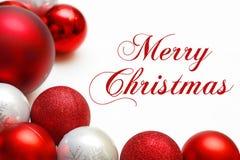 Grupp av trädprydnader som inramar text för glad jul Fotografering för Bildbyråer