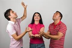 Grupp av tre folk som fångar något Royaltyfri Bild