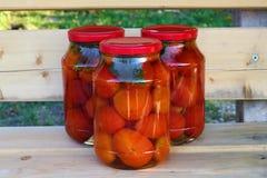 Grupp av tre glass cans av röda tomater på träbänken Fotografering för Bildbyråer