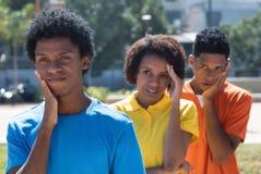 Grupp av tre ledsna afrikansk amerikanbarnvuxna människor arkivfoton