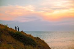 Grupp av tre personer som står på kullen nära havet som ser solnedgång royaltyfria foton