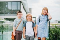 Grupp av tre roliga ungar som bär ryggsäckar som tillbaka går till skolan Fotografering för Bildbyråer