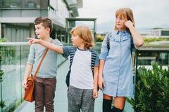 Grupp av tre roliga ungar som bär ryggsäckar som tillbaka går till skolan Royaltyfria Foton