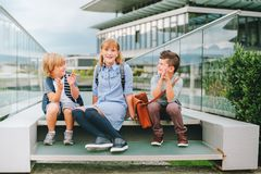 Grupp av tre roliga ungar som bär ryggsäckar som tillbaka går till skolan Royaltyfri Fotografi