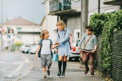 Grupp av tre roliga ungar som bär ryggsäckar som tillbaka går till skolan Royaltyfria Bilder