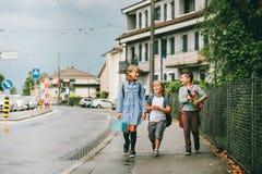 Grupp av tre roliga ungar som bär ryggsäckar som tillbaka går till skolan Arkivbild