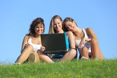 Grupp av tre tonåringflickor som skrattar, medan hålla ögonen på den utomhus- bärbara datorn Arkivfoton