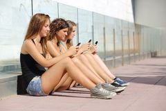 Grupp av tre tonåringflickor som skriver på mobiltelefonen