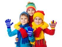 Grupp av tre ungar i vinterkläder Arkivbild