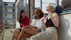 Grupp av tre vänner som hemma talar i terrass