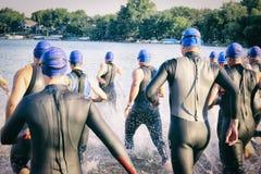 Grupp av Triathletes med körningar för blåttbadlock in i sjön för lopp Arkivfoto