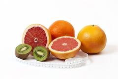 Grupp av tropiska frukter och måttband i cm Arkivbild