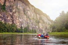 Grupp av turister som har fritid som rafting på den uppblåsbara katamaran vid floden längs en stenig kust Royaltyfri Foto