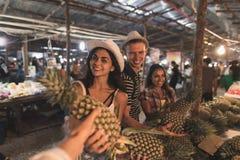 Grupp av turister som köper ananas på tropisk gatamarknad i Thailand ungdomarsom shoppar nya frukter Arkivfoton