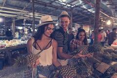 Grupp av turister som väljer ananas på tropisk gatamarknad i Thailand gladlynta ungdomarsom köper nya frukter Royaltyfri Bild