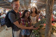 Grupp av turister som väljer ananas på tropisk gatamarknad i Thailand ungdomarsom köper nya frukter Royaltyfri Foto