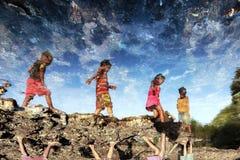 Grupp av u-landbarnlek på stranden arkivbild