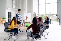 Grupp av ung asiatisk idérik lagsamtal-, leende- och skrattidékläckning som delar eller utbildar på möte eller seminarium på kont royaltyfri bild