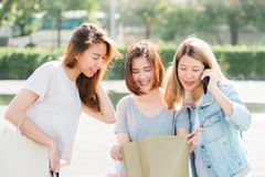 Grupp av ung asiatisk kvinnashopping i en utomhus- marknad med shoppingpåsar i deras händer royaltyfri fotografi