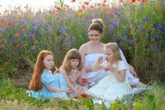 Grupp av ung flickavänner som har en picknick med lycklig modersi arkivfoton