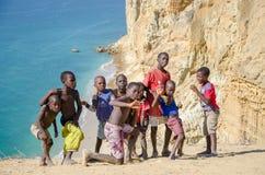 Grupp av unga afrikanska pojkar som framme poserar av spektakulär det ökenkustlinje och havet på Praia da Caotinha Royaltyfri Bild