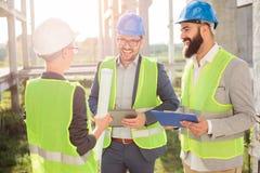 Grupp av unga arkitekter eller affärspartners som möter på en konstruktionsplats arkivbild