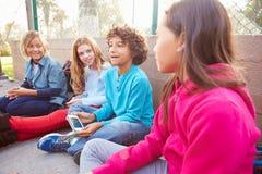 Grupp av unga barn som ut hänger i lekplats Arkivbild