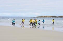 Grupp av unga barn som ut kör till havet för att surfa kurs Royaltyfria Foton