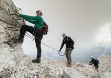 Grupp av unga bergsbestigare på ett brant via Ferrata med en storstilad sikt av de italienska dolomitesna arkivfoton