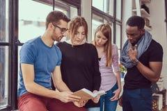 Grupp av unga blandras- studenter som arbetar med böcker och telefonen Fotografering för Bildbyråer