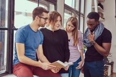 Grupp av unga blandras- studenter som arbetar med böcker och telefonen Royaltyfria Foton