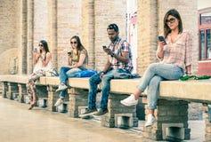 Grupp av unga blandras- vänner som använder smartphonen Arkivbild
