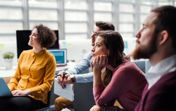 Grupp av unga businesspeople i regeringsst?llning som lyssnar till en presentation royaltyfri fotografi