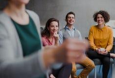 Grupp av unga businesspeople i regeringsst?llning som lyssnar till en presentation arkivfoto