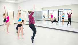 Grupp av unga dansare som framme öva av spegeln Arkivfoto