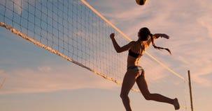 Grupp av unga flickor som spelar strandvolleyboll under solnedgången eller soluppgång, ultrarapid, arkivfilmer