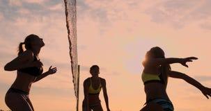 Grupp av unga flickor som spelar strandvolleyboll under solnedgången eller soluppgång, ultrarapid, stock video