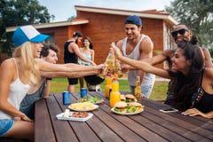 Grupp av unga gladlynta vänner som har gyckel på picknicken utomhus Arkivbild