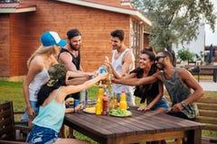 Grupp av unga gladlynta vänner som har gyckel på picknicken utomhus Arkivfoton
