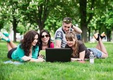 Grupp av unga högskolestudenter som sitter på gräs royaltyfria foton