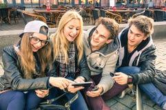 Grupp av unga hipstervänner som har gyckel med smartphones Arkivfoton