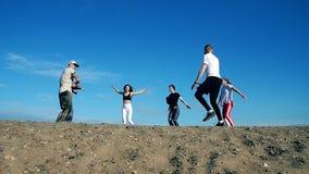 Grupp av unga idrottsman nen som hoppar och lyfter deras armar upp i luften mot blå himmel, ultrarapid stock video