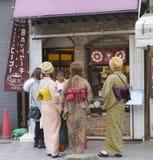 Grupp av unga japanska kvinnor iklädd kimono, fönstershopping Asakusa Japan, 2018 arkivfoto