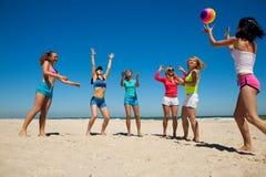 Grupp av unga joyful flickor som leker volleyboll Royaltyfri Fotografi
