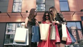 Grupp av unga kvinnliga vänner som till varandra visar deras köp stock video