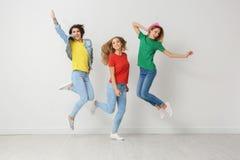 Grupp av unga kvinnor i jeans och färgrika t-skjortor royaltyfria bilder