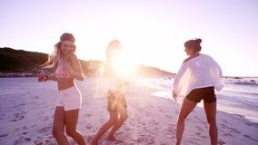 Grupp av unga kvinnor som dansar på stranden