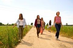 Grupp av unga kvinnor som går på ett fält av vildblommor royaltyfri bild